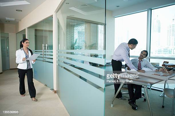 Businesswoman looking at businessman working in office
