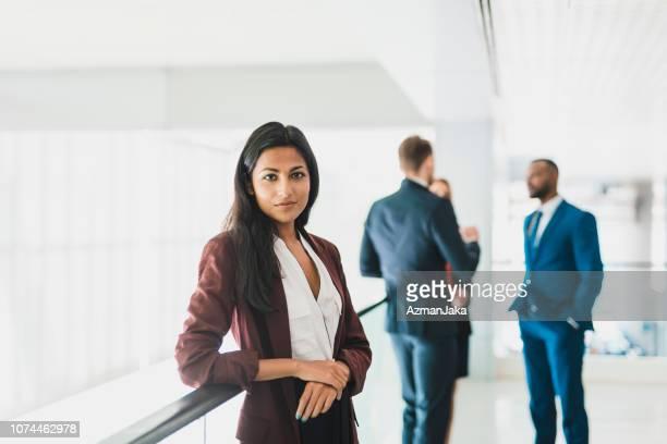 カメラと彼女の背後に話してビジネスマンのグループを見て実業家