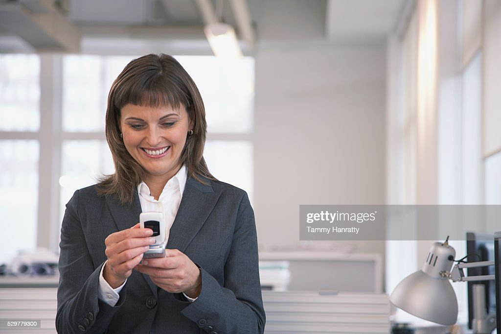 Businesswoman looking at cell phone : Stock Photo