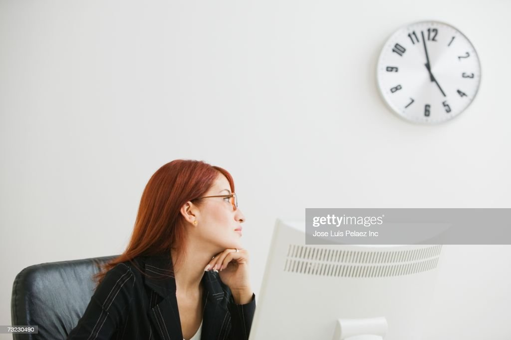 businesswoman looking at clock stock photo getty images