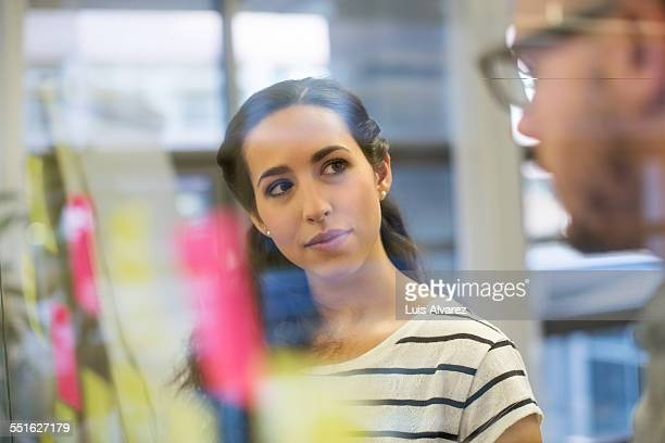 Businesswoman looking at colleague by glass wall