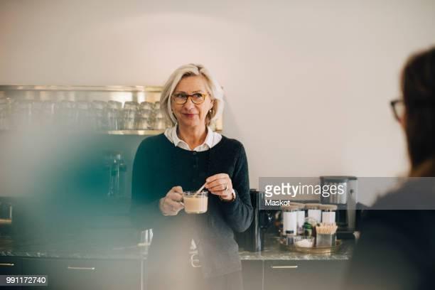 businesswoman looking at colleague while making tea in office - koffiepauze stockfoto's en -beelden