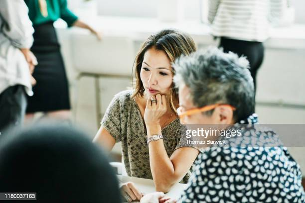 businesswoman looking at data on laptop during meeting in coworking office - challenge stock pictures, royalty-free photos & images