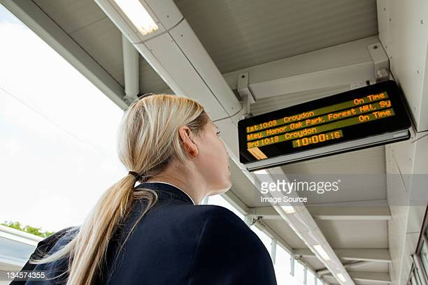 Businesswoman looking at departure board in station