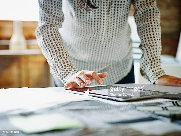 businesswoman looking at digital tablet in office - effectiviteit stockfoto's en -beelden