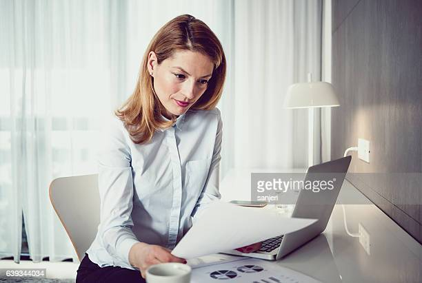 Businesswoman Looking at Documents and Using Laptop