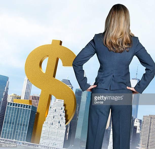 Femme d'affaires regardant Dollar debout de fraîcheur parmi les gratte-ciel