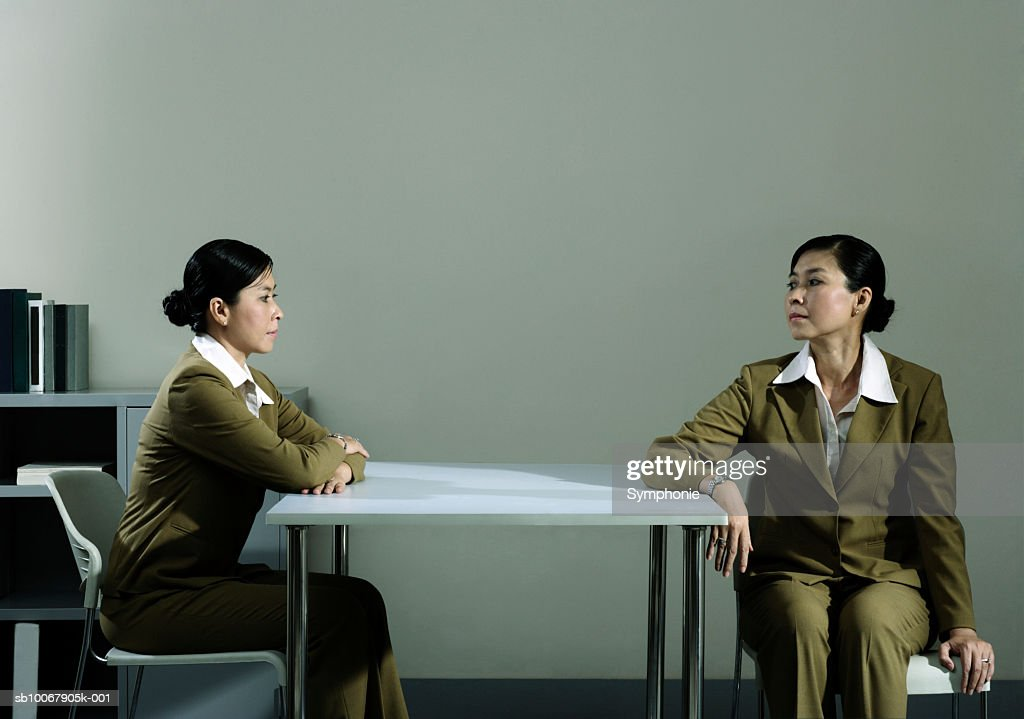Businesswoman looking at duplicate sitting at table in office (Digital Composite) : Stock Photo