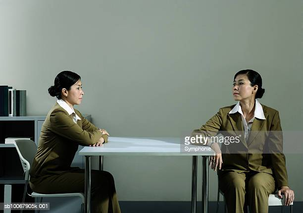 Businesswoman looking at duplicate sitting at table in office (Digital Composite)