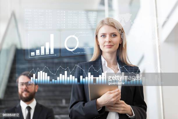 Businesswoman looking at financial data on futuristic display