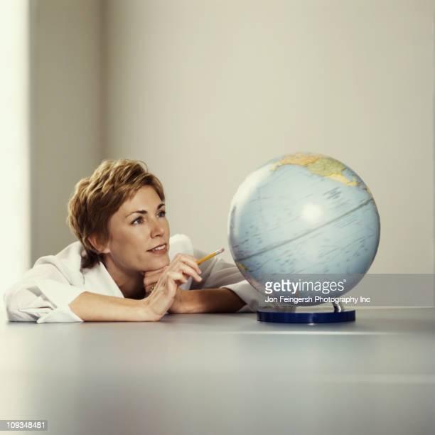 donna d'affari alla ricerca al mondo - mappamondo foto e immagini stock