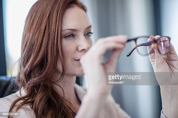 Businesswoman looking at her glasses