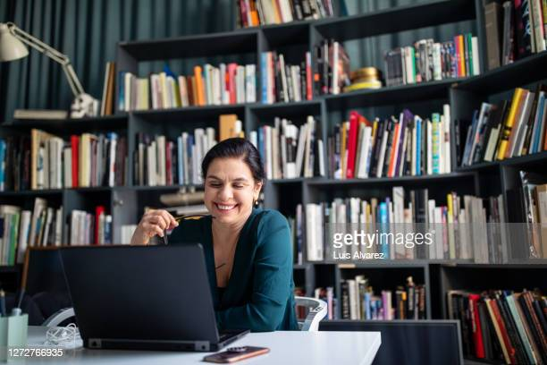 businesswoman looking at her laptop and smiling - development stock pictures, royalty-free photos & images