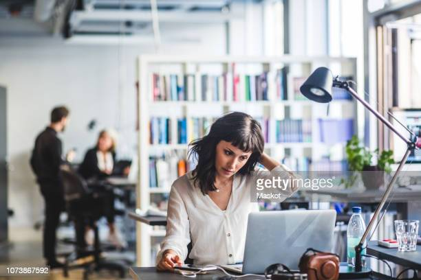 businesswoman looking at laptop while sitting in office - werkgelegenheid en arbeid stockfoto's en -beelden