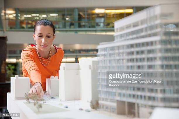 Businesswoman looking at model building