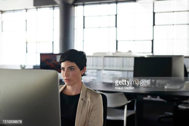 businesswoman looking at monitor in office - cream coloured blazer stock pictures, royalty-free photos & images