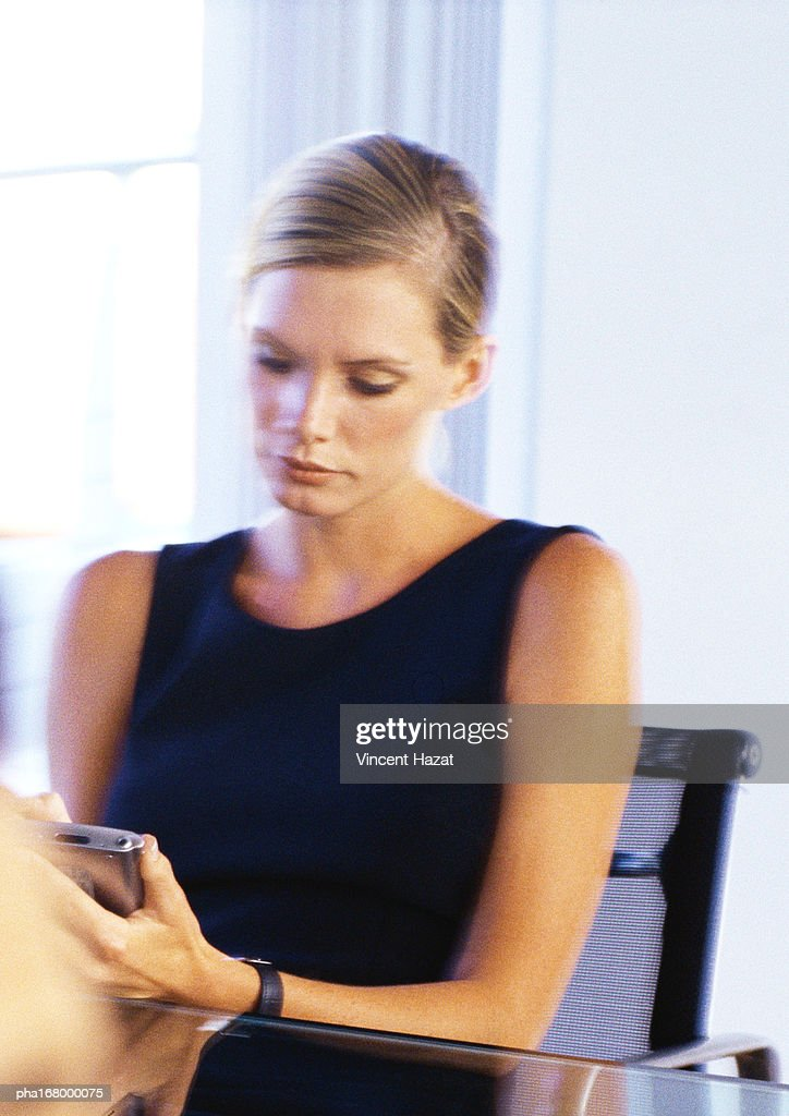 Businesswoman looking at pocket computer : Stockfoto
