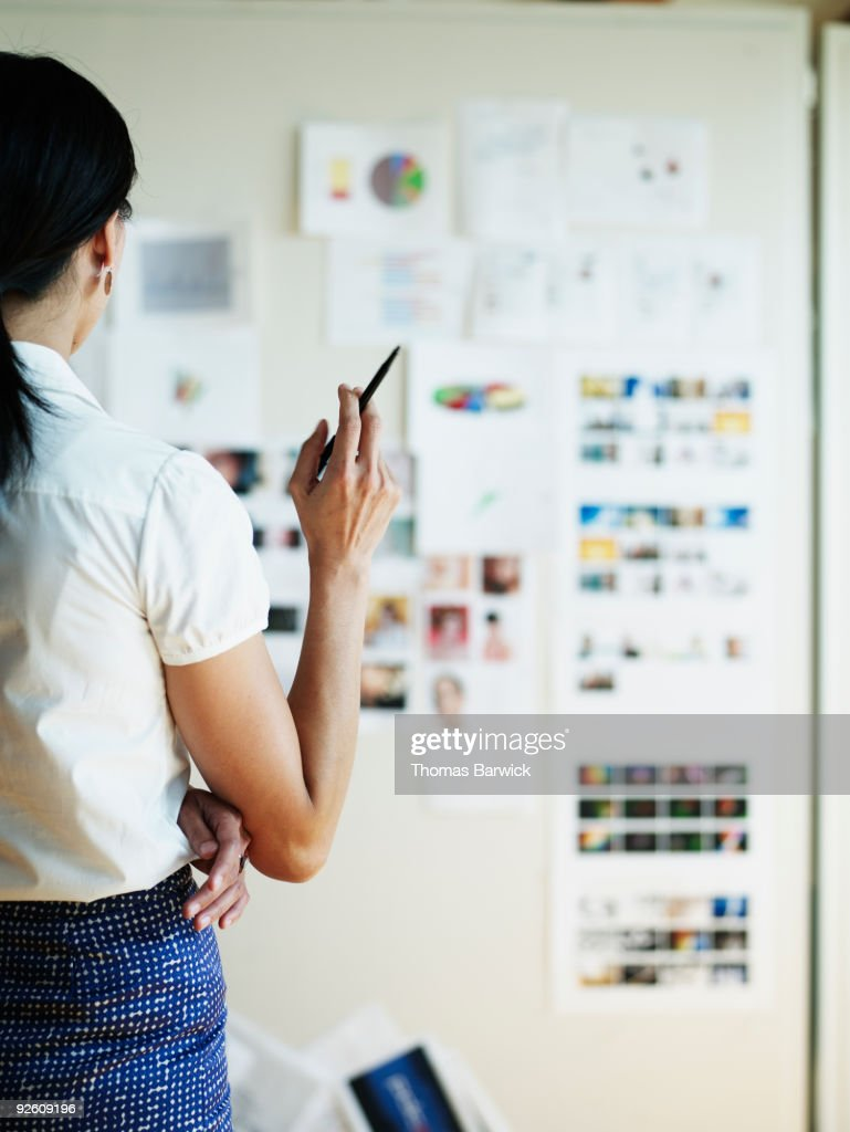 Businesswoman looking at project board rearview : Stock Photo
