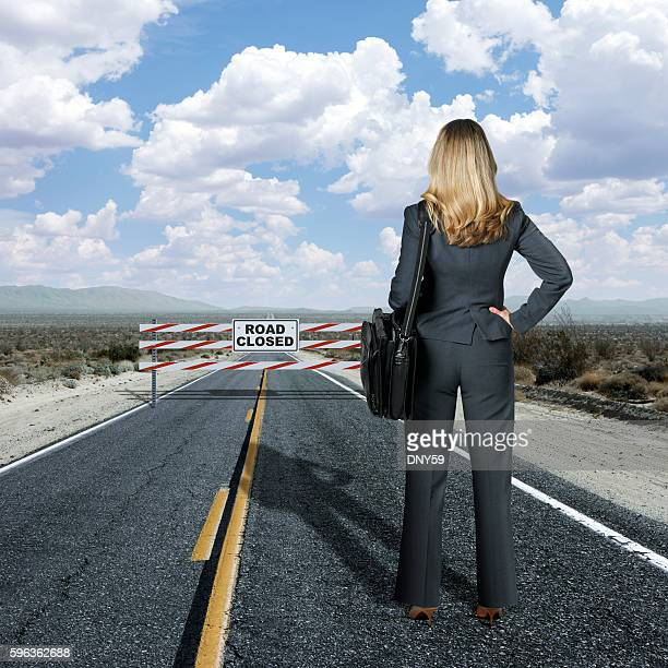 Businesswoman Looking At Road Block On Long Staight Highway