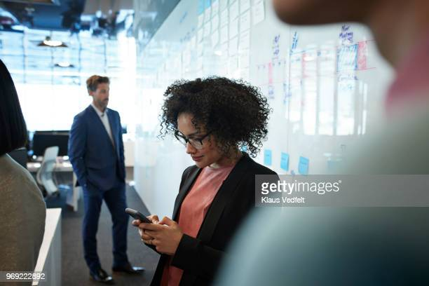 businesswoman looking at smartphone inside creative office - images fotografías e imágenes de stock