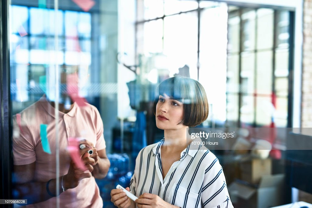 Businesswoman looking at sticky notes with curious expression : Stock Photo