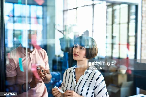 businesswoman looking at sticky notes with curious expression - neu stock-fotos und bilder