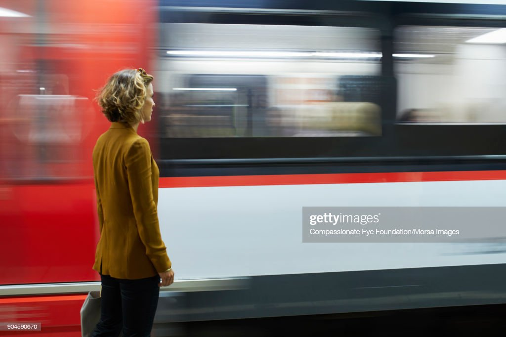 Businesswoman looking at subway train : Stock Photo