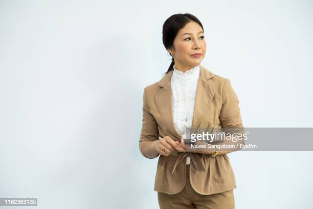 businesswoman looking away and holding digital tablet while standing against white background - businesswear stock pictures, royalty-free photos & images