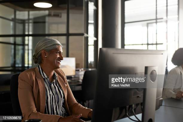 businesswoman looking away at modern office desk - striped blazer stock pictures, royalty-free photos & images