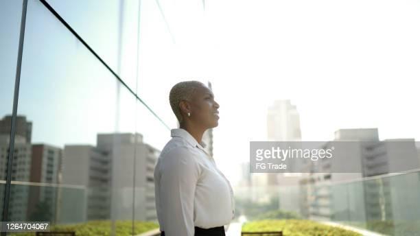 empresária olhando para longe contemplando e pensando no telhado do escritório - ir adiante - fotografias e filmes do acervo