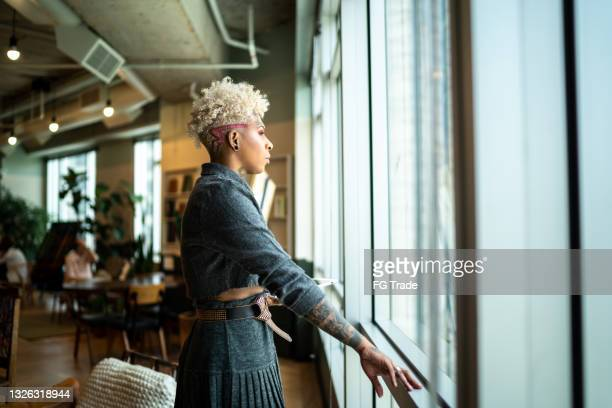businesswoman looking away contemplating at the office - cultures stock pictures, royalty-free photos & images