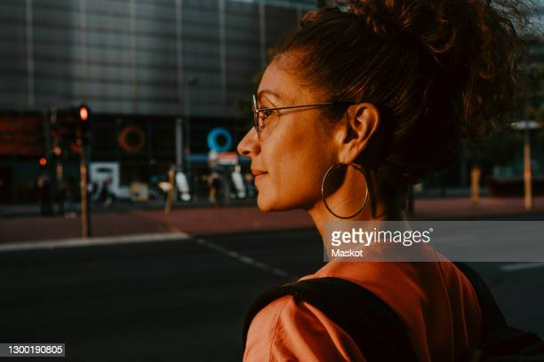 businesswoman looking away in city during sunset - crossing stock pictures, royalty-free photos & images