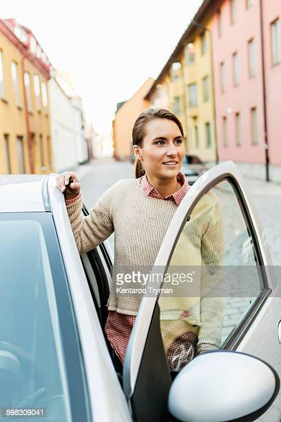 Businesswoman looking away while entering car on street