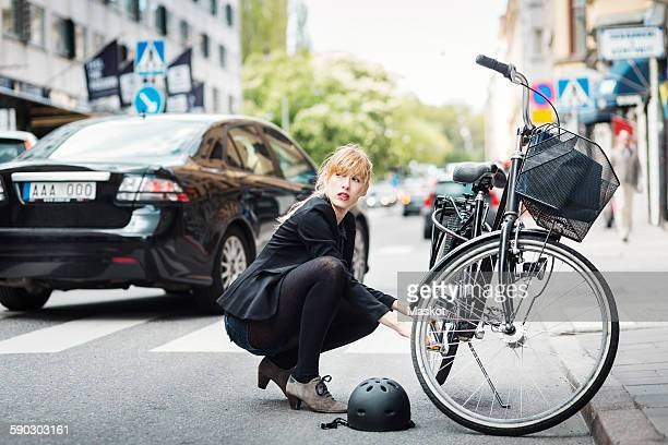 Businesswoman looking away while repairing bicycle on street