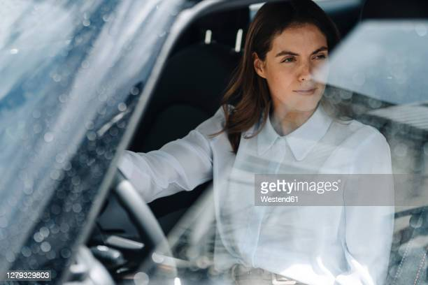 businesswoman looking away while sitting in car - entering stock pictures, royalty-free photos & images