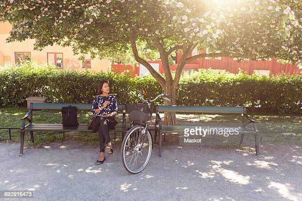 Businesswoman looking away while sitting on park bench