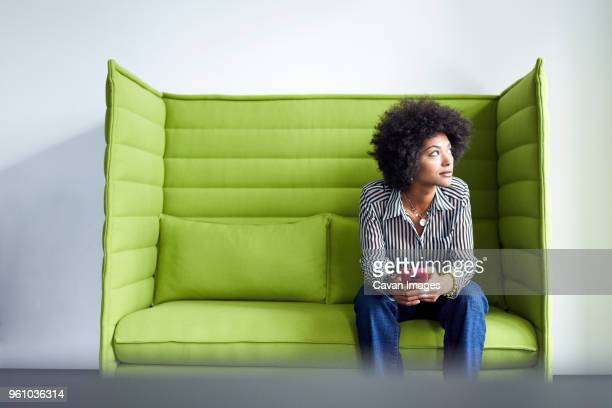 businesswoman looking away while sitting on sofa against wall in office - capelli neri foto e immagini stock