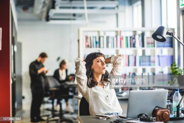 businesswoman looking away while sitting with hands behind head at desk in office - mid adult women stock pictures, royalty-free photos & images