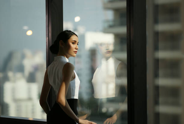 businesswoman looking away while standing by window at office - asian woman in the office stock pictures, royalty-free photos & images