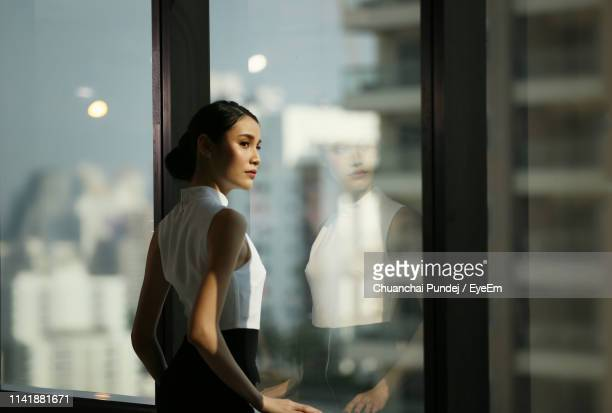businesswoman looking away while standing by window at office - abbigliamento elegante foto e immagini stock