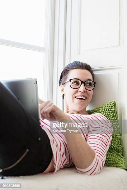 Businesswoman looking away while using digital tablet on window seat in creative office
