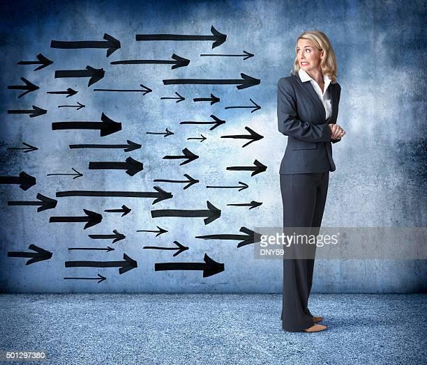 Mulher de Negócios olhando para trás em grupo de setas aproximação