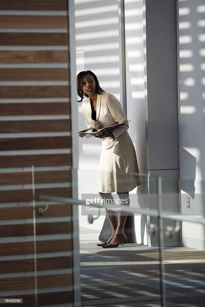 Businesswoman looking down hall : Stockfoto