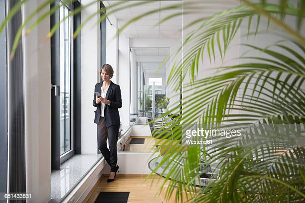 Businesswoman looking on cell phone at office window