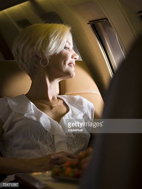 A businesswoman looking out an airplane window