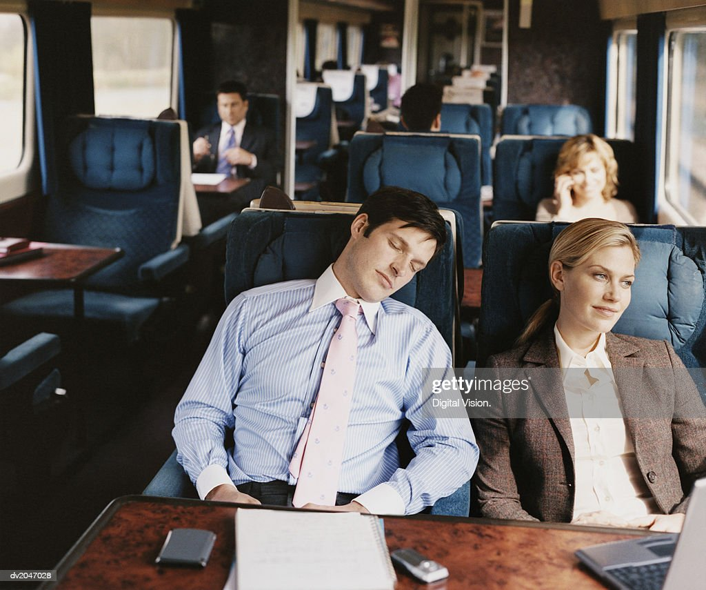 Businesswoman Looking Out of a Passenger Train Window and Sitting Next to a Sleeping Businessman : Stock Photo
