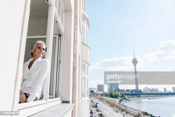 Businesswoman looking out of window in waterfront office