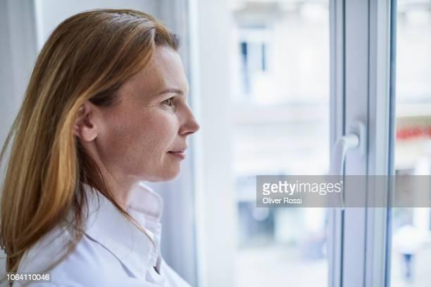 businesswoman looking out of window - profil stock-fotos und bilder