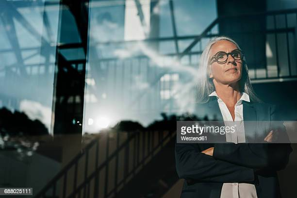 businesswoman looking out of window - directrice photos et images de collection