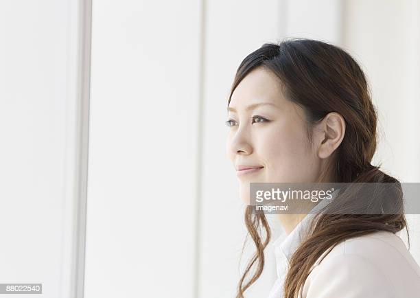 businesswoman looking out of window - 横顔 ストックフォトと画像
